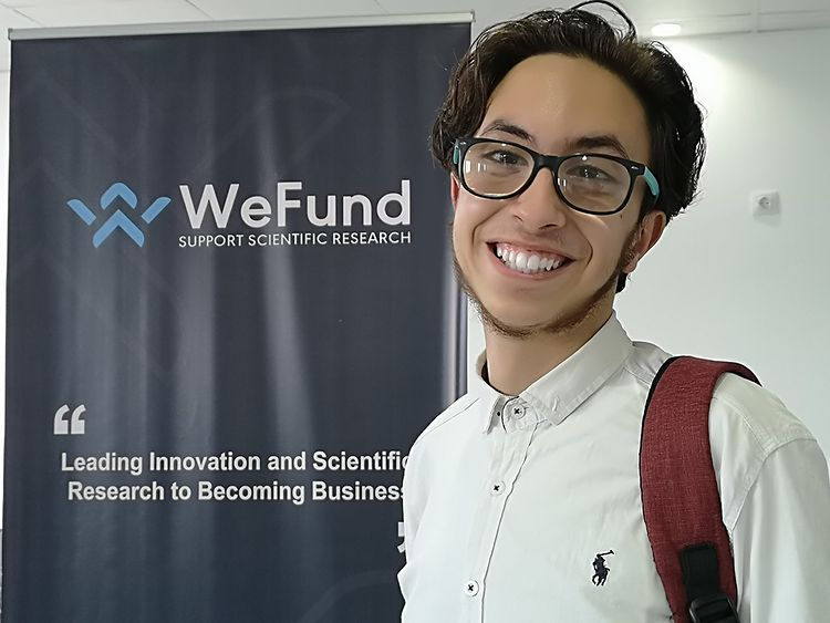 Mohamed smiling and standing in front of a WeFund banner